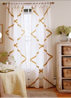 Add drama to a room by hanging tab-top panels embellished with a grid of ribbon and rickrack. Choosing natural colors and textures keeps the boldness of the pattern in check. Measure carefully and plan ahead for proper ribbon placement.  Glue down ribbon. needed, wrap it around the edge of the curtain.   Tip: Before adding embellishments, first press the draperies. Accurate positioning of ribbons and trims will be easier on a smooth surface.