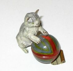 An early 20th century painted metal tape measure in the form of a cat