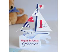 ** Due to popular demand new larger size **  An original and unique personalised handmade card of a sailing boat for a baby boys 1st birthday. When opened a sailing boat takes shape with a sail and bunting. All text can be personalised.  Message area on the back .  Made from good quality 250 GSM card.  Supplied with 162 x 229mm white envelope and cellophane wrapped. Message me your text for the card when ordering.  Packaged carefully in a hard backed envelope.  Designed and hand cut by me in…