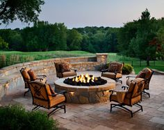 An outdoor living space in Leawood, Kan., features a round fire pit on a paver patio. The fire pit and patio use Belgard's Mega Lafitt pavers and stones, which have the texture and look of cut flagstone.