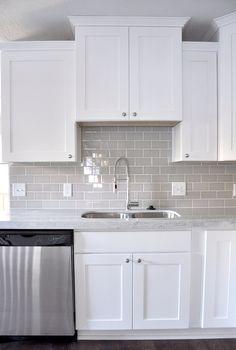 Smoke Gray glass subway tile, white shaker cabinets.