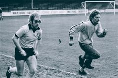 Elton John and good friend Rod Stewart race during a Watford Football Club practice, 1973.