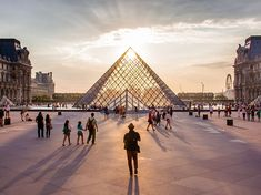 Aglow in the City of Light Photograph by Noemie Trusty - Sun shining through the Louvre Pyramid in Paris, France.