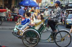 Today's feature street photo is of a human powered rickshaw as it darts through a busy intersection carrying a Khmer family in Phnom Penh, Cambodia. Battambang, Cambodia Travel, Phnom Penh, Angkor, Street Photo, Darts, Carry On, Travel Inspiration, Hand Luggage