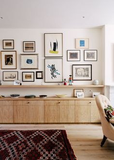 This gallery wall combines modern art with old photographs and maps to create a contemporary display that shows off the home owner's many interests.