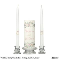 """Wedding Unity Candle Set   Spring Boho Florals Boho style wedding unity candle set features a script monogram of the bride and groom names, accented with romantic flowers, botanical leaves, and rustic bird feather accents. Additional """"Love"""" with peony flower and custom wedding date text appears on the taper candles. Soft color scheme includes shades of pink, peach, cream, green, gray, and gold. The light ivory printed background color can be customized."""