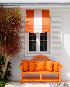 """Amanda Lindroth gave the exterior """"a showstopping personality"""" with big splashes of bold orange. Bench in Sherwin-Williams's Knockout Orange. Pillows in a Link Outdoor canvas. Awning fabric, Sattler."""