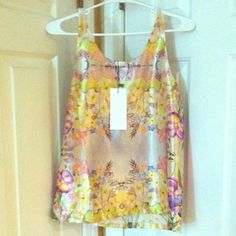 SILK FLORAL TANK TOP - NWT Colorful silk-like yellow tank top with floral designs on it. The back has a sequin/beaded detailing on it. Has never been worn before!!!! Can for a small perfectly and on an x-small it would be slightly loose. OFFERS WELCOME! Lulu's Tops Tank Tops
