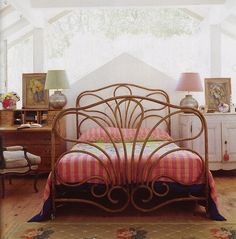 rattan bed frame, matching lamps with mismatched shades and a secretary desk as bedside table (midcenturyjo on Flickr)