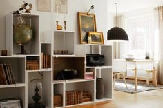Oh I love how these square and rectangular boxes are used to create a unique and architectural shelving unit.