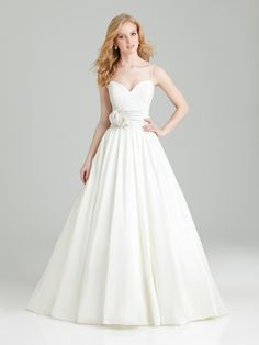 Soft and romantic. This ball gown features a sweetheart neckline and spaghetti straps while lace adorns the bodice. Ruched taffeta and delicate flowers accent the natural waistline.