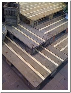 Wooden deck designed entirely of industrial pallets which are a stronger, more durable pallet.  The spaces are filled with 1x boards cut to fit.