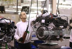 An employee controls a winch as he maneuvers an Aston Martin automobile engine following production at Aston Martin Lagonda Ltd.'s manufacturing and assembly plant in Gaydon, U.K., on Wednesday, Dec. 10, 2014. Aston Martin, which sold 4,200 vehicles last year, is in the midst of the biggest expansion in its 101-year history after London-based investment firm Investindustrial bought a 37.5 percent stake in December 2012. Photographer: Chris Ratcliffe/Bloomberg via Getty Images