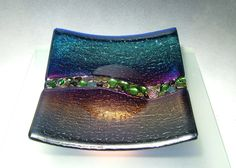 A fused and slumped plate with unique glass rock fused into the middle, gives the effect of a flowing riverbed. This plate was also handcrafted in our studio, and is sure to be a collectible. It measures approximately 9 1/2 x 9 1/2 and comes with a stand for displaying in your home or office space.