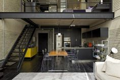 Slight industrial feeling loft with black hardwood floors. Concrete walls, Structural steel, and electrical pipe exposed.