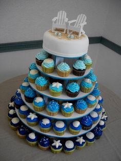 """Beach Wedding Cupcake Tower - This cupcake tower was done for a beach themed wedding reception.  Cake topper is covered in fondant with graham cracker """"sand"""".  Chairs are wooden; flip flops are fondant.  Cupcakes are iced with buttercream and decorated with sugar pearls and white chocolate molded shells.  TYFL!"""