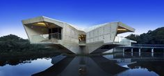 futuristic concrete house with bridge access and eco appeal.