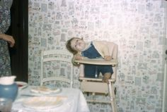 Colour transparency slide of Jayne Turner in a highchair with her head tilted to one side and bright patterned wallpaper in the background, in the kitchen of her family home at 182 Whittington Way, Pinner, Middlesex. The photograph was taken by Selwyn Turner between 1958 and 1959. This is one item in the Documenting Homes collection (168/2011-1 to –85) from Alec Turner.