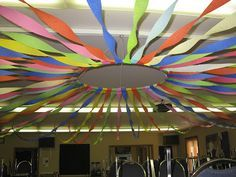 It starts with a hula-hoop and several roles of crepe paper. Once you have them all attached to the hula-hoop you raise it into place and then twirl and attach all the streamers to the walls.