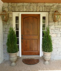 Wood front door, urn planters, brass carriage lanterns, stone wall