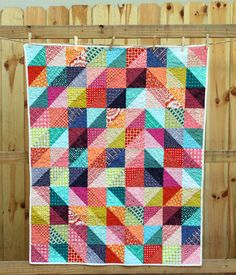 """This bright fun baby quilt uses half-square triangles arranged in an off-center radiating diamond shape in hues of pink, teal, navy, orange, lime, and purple. The pattern emerges thanks to pairing light and dark values of the same color together.  The quilt measures 36"""" x 46"""""""