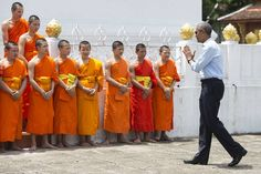 President Barack Obama greeted monks on Wednesday as he tours the Wat Xieng Thong Buddhist Temple in Luang Prabang, Laos (Photo by AFP).