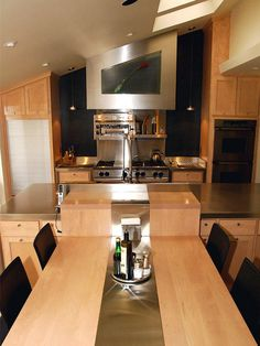 How do you fit professional appliances into a tiny space? Challenged by unusual angles and cramped quarters, these homeowners designed a narrow workspace footprint where every inch of space was an opportunity to be creative. Using blonde wood, stainless steel and spot lighting the kitchen has become an organic work of modern art. The table is a harmonious extension of the island, where the sink sits. On the left of the oven is a tambour door