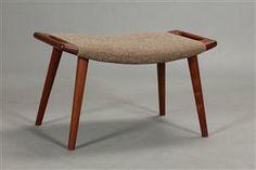Hans J. Wegner 1914-2007. Skammel med stel og ben af teak. Betrukket med uld. (Passer til bamsestolen) Formgivet i 1954. Fremstillet hos AP-Stolen, model AP-19 Vurd. 8000 kr
