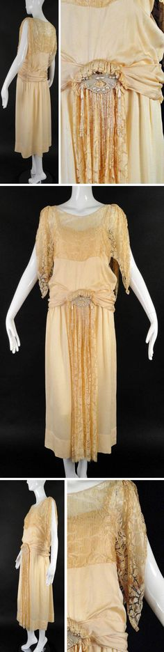 Wedding gown ca. 1920s. Ivory silk de chine. Narrow shoulder straps and blouson bodice. Ivory lace attached across chest; scoop neckline. Handkerchief sleeves fall from gathers at shoulders. Silk sash in pleats from center front. Slender skirt falls from dropped waistline with slight gathers. Center front adornment in ivory lace is pleated across top and has white bead & pearl appliqué medallion with bead and pearl fringe beneath. Side snap closures. Vintage Martini