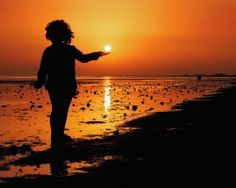Young girl holding the sun in palm of her hand.