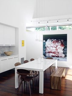 Dining room with white lacquer table, Cherner chairs, and a large artwork