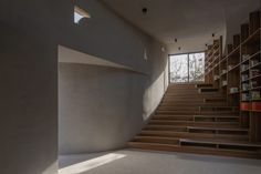 Inside the building, the compact ground floor can be used as a projection room and reading space, with bookshelves and bench seating incorporated into the curving stair. Concrete Forms, Concrete Houses, Concrete Walls, Chinese Architecture, Contemporary Architecture, Derelict House, Large Curtains, Rammed Earth Wall, Old Home Remodel