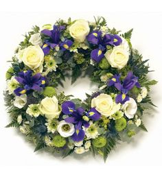 A purple and white wreath featuring blue Iris, white Roses, Lisianthus and Chrysanthemums.