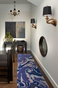 A glass porthole looks from the kitchen to second floor hallway, which features a swirling grape runner designed by Chicago painter Lynn Basa.