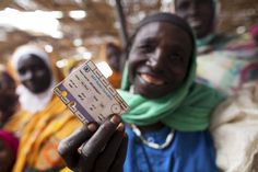 WFP Distributes Food Vouchers to Darfur Displaced. A woman flashes her ration card at the voucher distribution centre at Abu Shouk Camp for Internally Displaced Persons (IDPs) in North Darfur, Sudan. 18 October 2012. UN Photo/Albert González Farran