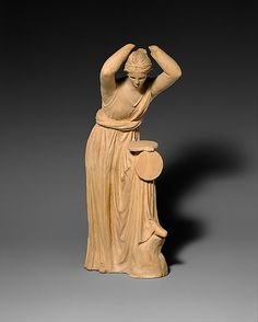 Terracotta Statue of a Woman looking into a Box Mirror    300-200 BC    Hellenistic    This woman holds a box mirror on her knee. The lid has dropped and she gazes into the reflective surface, which would have been of highly polished bronze.