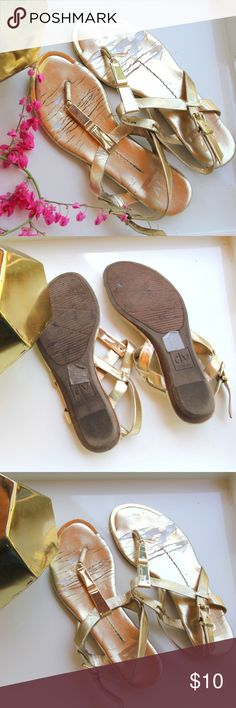 DV DOLCE VITA Metallic Gold Sandals DV Dolce Vita gold sandals with a metallic gold piece in the middle. Adjustable straps over the heels. Good grip on the bottom of the shoe and a slight rise for padded comfort. The wear on the inside of the sandals are shown in the photos. DV by Dolce Vita Shoes Sandals