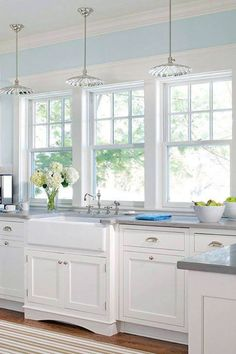 three windows over sink area no lower panes gooseneck lighting over each one at wall white cabinets farmhouse skirted sink pulled out a bit and bottom : sink windows window love