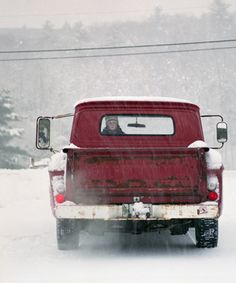 Red truck on a snowy road. Look at the little face looking out the back window. Hope it's parked! LOL!
