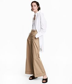 Beige. Vide bukser i bomuldsblandet twill. Bukserne har forlænget linning med metalspænde foroven, sidelommer og paspolerede baglommer. Lige ben med