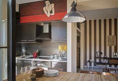 Cucina a vista su misura nei toni del grigio piombo e un ampio tavolo Danton di Cargo con top in teak di recupero ricreano un'atmosfera vissuta e autentica nella zona giorno dell'appartamento per uno di Osnago. A riqualificarlo Studio76 Architetti