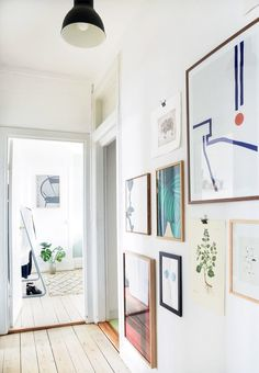 Beautiful hallway with botanical posters and graphic illustrations from floor to ceiling.