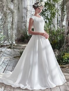 Maggie Sottero - anita marie, Rich Shavon organza adds an exquisite dose of romantic elegance to this voluminous A-line wedding dress, detailed with covered buttons trailing from neck to hemline. Finished with cap-sleeves, soft scoop pleated neckline, hidden pockets, and covered buttons over zipper closure. Detachable beaded belt sold separately.