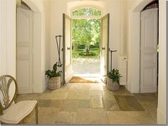 Here's an entry hall in a mas with double front doors and old stone floors