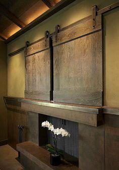 Badass sliding wooden door with rustic metal rails to hide your flat screen!