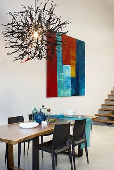 In this modern dining area, a wood dining table sits below a sculptural pendant light made from human-like figurines. A wall mounted painting with reds, blues, yellows, and whites ties in the various colors used throughout this modern loft interior.
