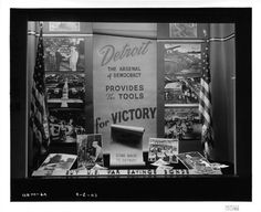 """""""Detroit, The Arsenal of Democracy Provides the Tools for Victory."""" Images from differing plants including Chrysler and Willow Run surround the signage and depict tanks, airplanes, and other war effort materials being produced."""