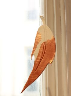 Learn how you can make stunning copper dipped clay feathers to hang in your home or give as a gift