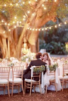 Bistro lights, lots of green and white plants and fabrics...outdoors with NO TENT! :), and the bride's and groom's chairs are backed with white ribbon and evergreen boughs lending elegance to this forest reception.