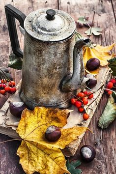 autumn still life - old book on wooden table on background of the kettle strewn with autumn leaves and Rowan.